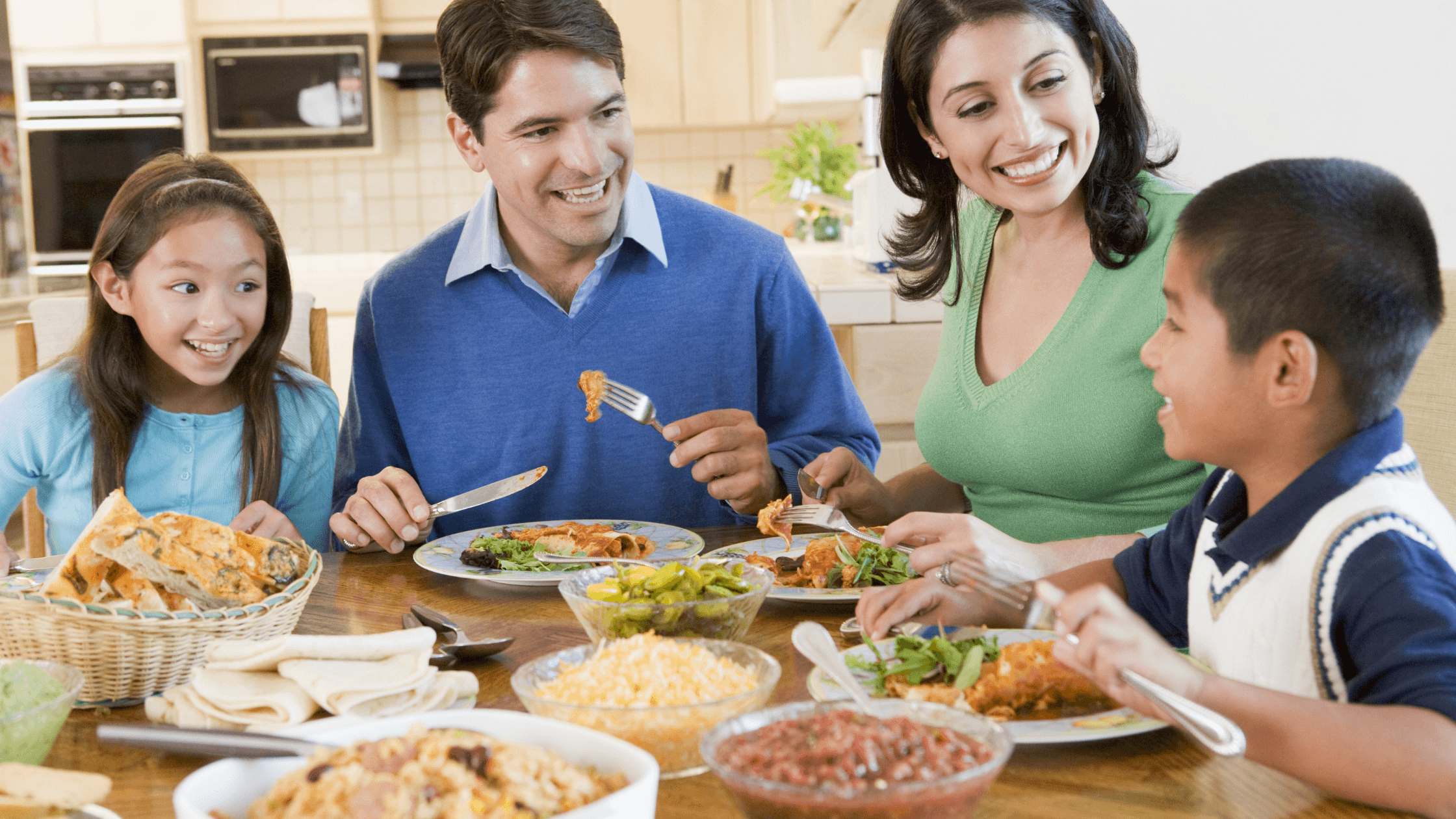 Hispanic family eating a meal and laughing